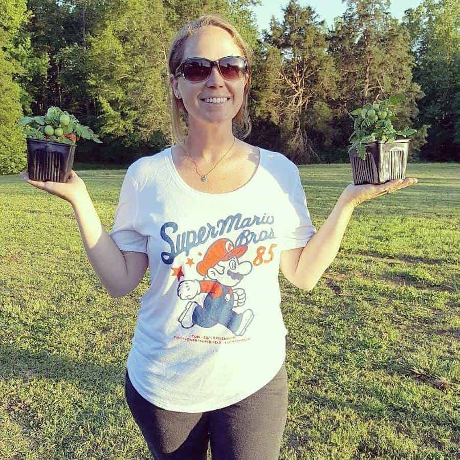Laura, author at Youshouldgrow.com, holding two miniature tomato plants.