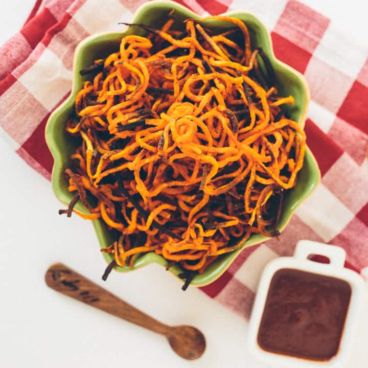 Spiralized sweet potato fries in bowl with sauce