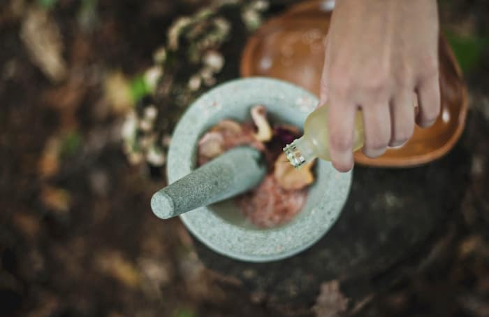 Dripping EO into mortar and pestle. Article with tips for safe essential oil use around kids